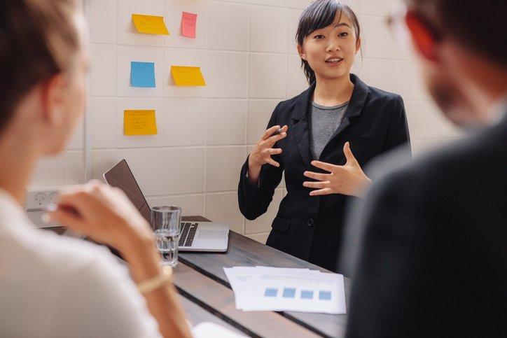Businesswoman standing by a wall with sticky notes leading a business presentation. Female executive putting her ideas on adhesive notes during a presentation in conference room.