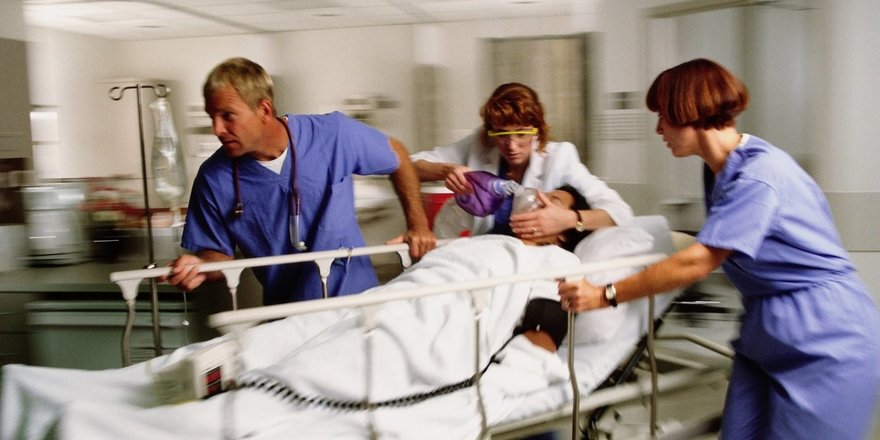 Wheeling an emergency patient through the hospital while a nurse administers oxygen
